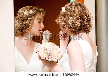 Beautiful young bride refreshing her makeup - stock photo