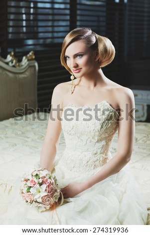 Beautiful young bride with makeup and fancy hairstyle in fancy dress sitting on bed - stock photo