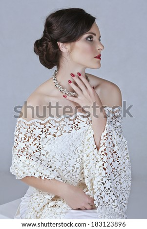 Beautiful young bride with wedding makeup in romantic lace dress on studio background - stock photo