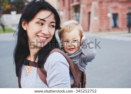 Beautiful young brunette asian woman with freckles and her blond son on walk. Unusual appearance and heredity concept. Baby sits in sling on mothers back and closes his ears because of noise - stock photo