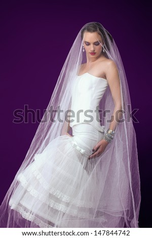 beautiful young brunette bride wearing wedding dress and corset under a veil against purple studio background
