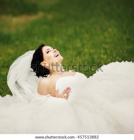 Beautiful young brunette bride wearing white dress laying on grass in garden - stock photo