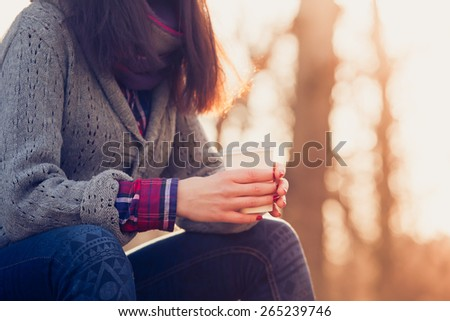Beautiful young brunette Caucasian woman drinking takeaway coffee in park in autumn. Pretty girl with sweater outdoors in fall with coffee cup
