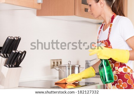 Beautiful young brunette cleaning the kitchen. attractive girl standing in apron and using detergents - stock photo