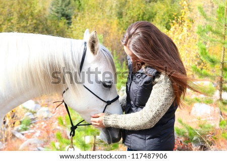 Beautiful young brunette cowgirl with her white horse - stock photo