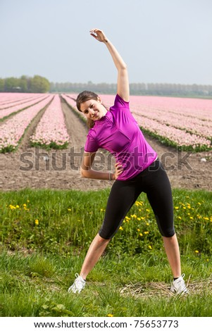 Beautiful young brunette doing stretch exercises outdoors - stock photo