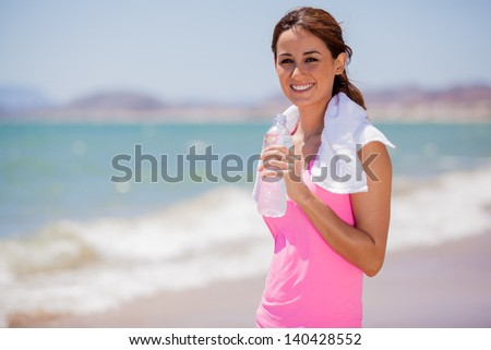 Beautiful young brunette drinking water and cooling off after running at the beach - stock photo