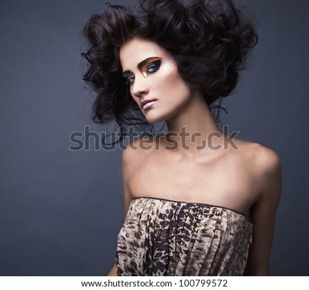 Beautiful young brunette female with bright fashion multicolored make-up. Studio photo. - stock photo