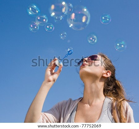 Beautiful young brunette girl blowing soap bubbles into the sky.