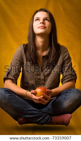 Beautiful young brunette girl doing yoga levitation holding an apple.