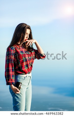 Beautiful young brunette girl in jeans and shirt standing on the beach.