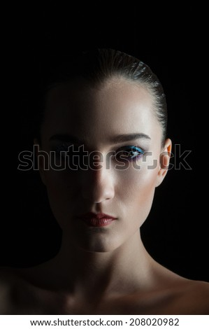 Beautiful young brunette girl isolated over black background. Darkness, shades on face. Fashion model