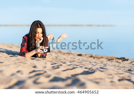 Beautiful young brunette girl lying on the sand on the beach with a camera and examines it.