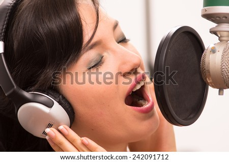 beautiful young brunette girl singing in music studio
