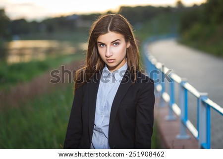 Beautiful young brunette girl standing alone outdoors - stock photo