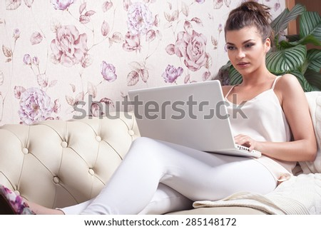 Beautiful young brunette girl using laptop at home, relaxing. - stock photo