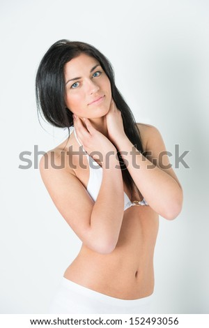 Beautiful young brunette girl wearing swimsuit. Posing against white wall background - stock photo