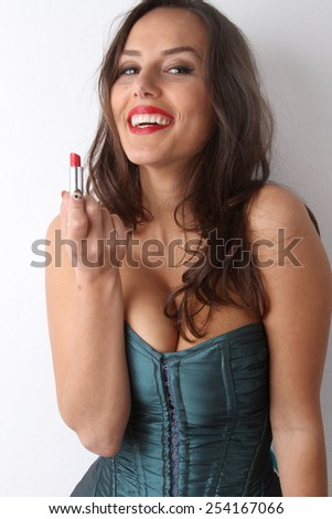 beautiful young brunette in a green blue corset with very red lipstick smiles and provocative posing for the camera with red lipstick in hand - stock photo