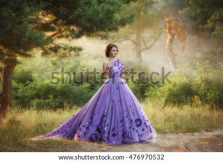 Beautiful, young, brunette in a luxurious, purple, long dress.  Fairy Photo. Creative toning. Queen walking in the fairy forest.