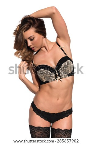 Beautiful young brunette in black and gold lingerie - stock photo