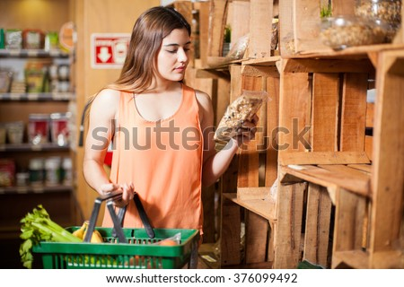 Beautiful young brunette looking at a product label while buying some groceries at the super market - stock photo