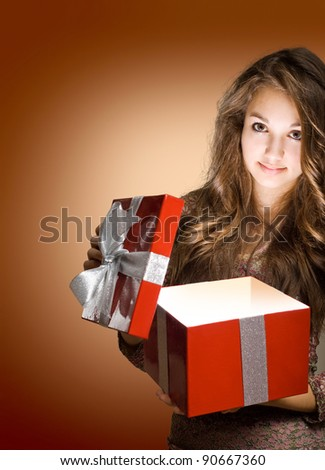 Beautiful young brunette opening big red gift box with light streaming out. - stock photo