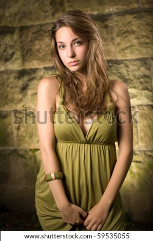 Beautiful young brunette posing outdoors in green dress.