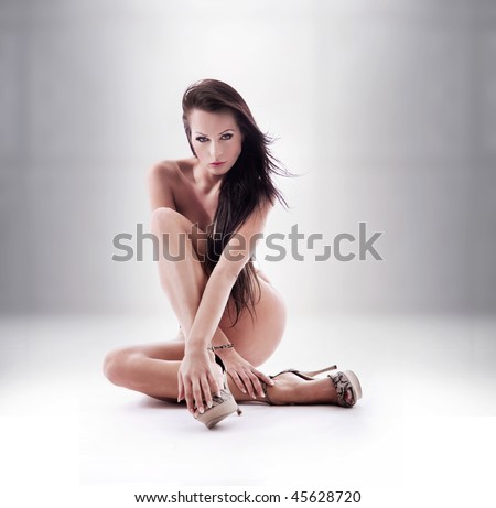 Beautiful young brunette posing over studio background - stock photo