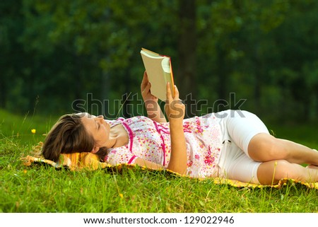 Beautiful young brunette reading on a meadow in the park - stock photo