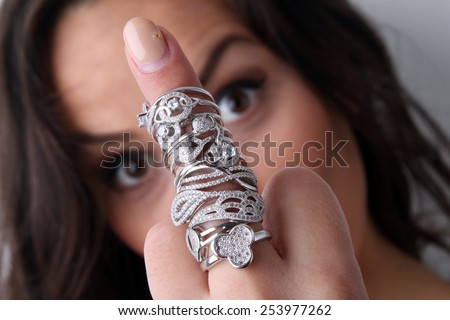 beautiful young brunette smiling girl showing lot of engagement rings and overjoyed by beautiful rings made of white gold with diamonds - showing middle finger - stock photo