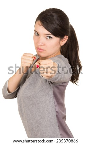 Beautiful young brunette strong confident girl posing punching to the camera fighting position isolated on white - stock photo