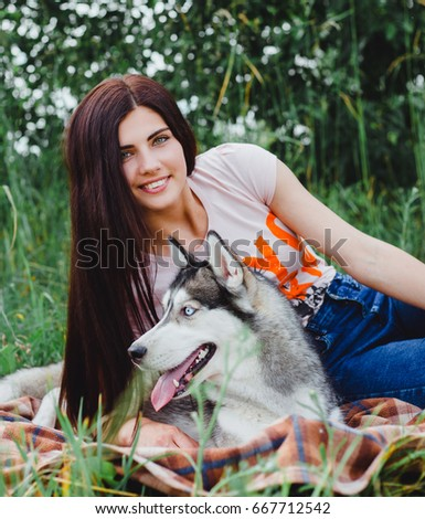 Beautiful young brunette with charming smile rests on a veil in the forest with a Husky dog