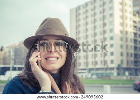 Beautiful young brunette with hat talking on phone in the city streets - stock photo
