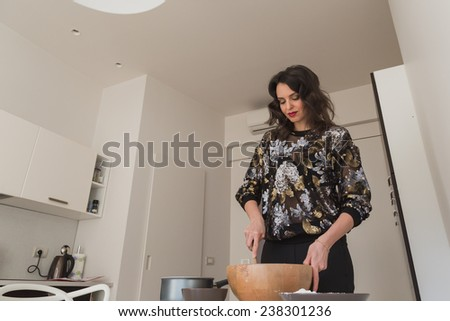 Beautiful young brunette with long hair cooking in the kitchen - stock photo