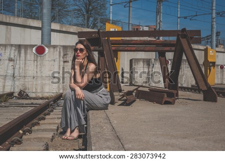 Beautiful young brunette with long hair posing along railroad tracks