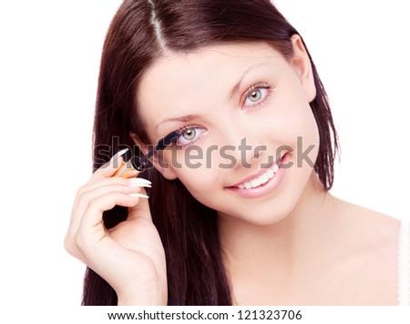 beautiful young brunette woman applying mascara on her eyelashes - stock photo