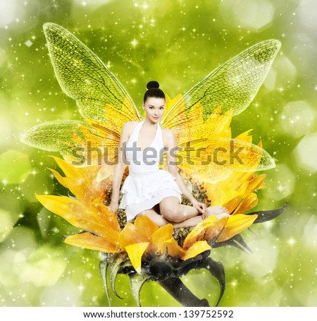 Beautiful young brunette woman as summer fairy on sunflower - stock photo