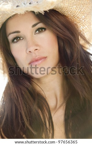 Beautiful young brunette woman backlit by sunshine and wearing a straw cowboy hat - stock photo