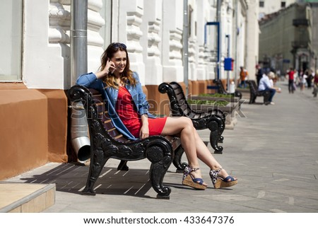 Beautiful young brunette woman calling by phone sitting on a bench outside in sunny weather