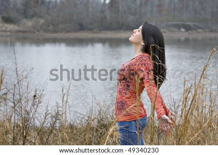 Beautiful young brunette woman deeply breathing in the fresh air with water and trees in the background - stock photo