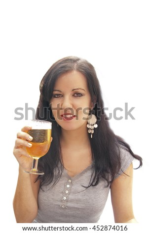 Beautiful young brunette woman drinking a beer - stock photo