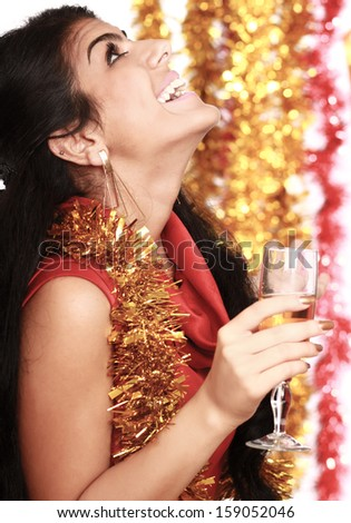 Beautiful young brunette woman drinking champagne at christmas party. Isolated on decorated background