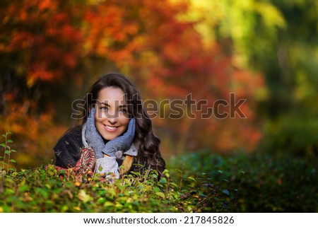 beautiful young brunette woman having a walk in the autumn park - stock photo