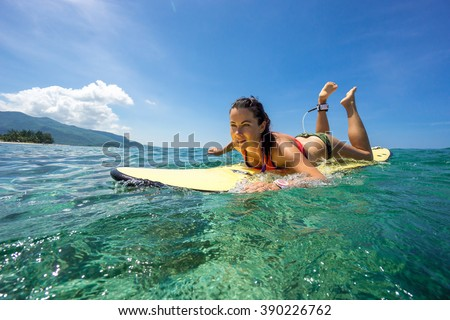 Beautiful young brunette woman in a bright bikini surfing in Mauritius in the Indian Ocean on the background of blue sky, clouds and transparent waves - stock photo