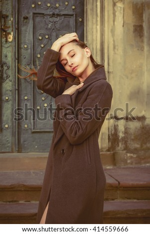 Beautiful young brunette woman in a grey coat at the street - stock photo