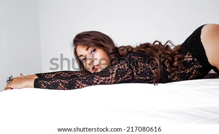 beautiful young brunette woman in bed at home - stock photo