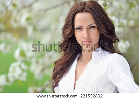 Beautiful young brunette woman in blooming garden - stock photo