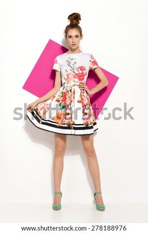 beautiful young brunette woman in nice colorful summer dress, high heels, bun, handbag posing in studio. Fashion photo - stock photo