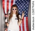 beautiful young brunette woman in style cloth and sunglasses with national usa flag in background - stock photo