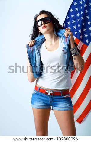 beautiful young brunette woman in style cloth and sunglasses with national usa flag in background with copyspace. 4th july concept - stock photo